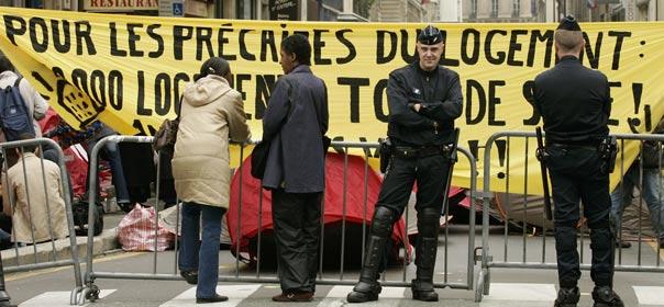 La police, devant une bannière de l'association Droit au logement (DAL), près de la Bourse, à Paris, le 4 octobre 2007. © REUTERS