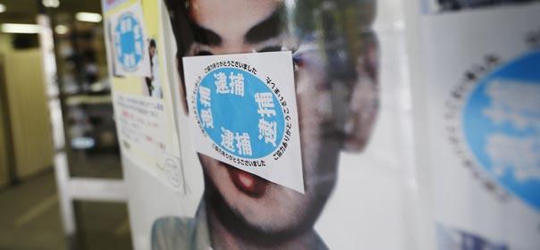 """Un autocollant affiche le mot """"Arrêté"""" sur le poster """"Recherché"""" de Katsuya Takahashi, dernier fugitif de la secte Aum, au commissariat de police de Tokyo. © REUTERS"""