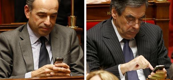 Combo de photos de Jean-François Copé (à gauche) et de François Fillon (à droite) utilisant leurs téléphones portables lors de la session des questions au gouvernement à l'Assemblée nationale, le 4 décembre 2012. © REUTERS