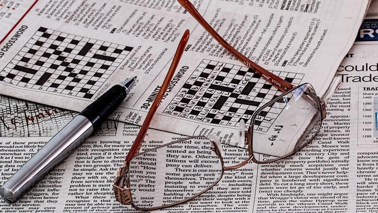 mots croisés, lunettes, journal, stylo